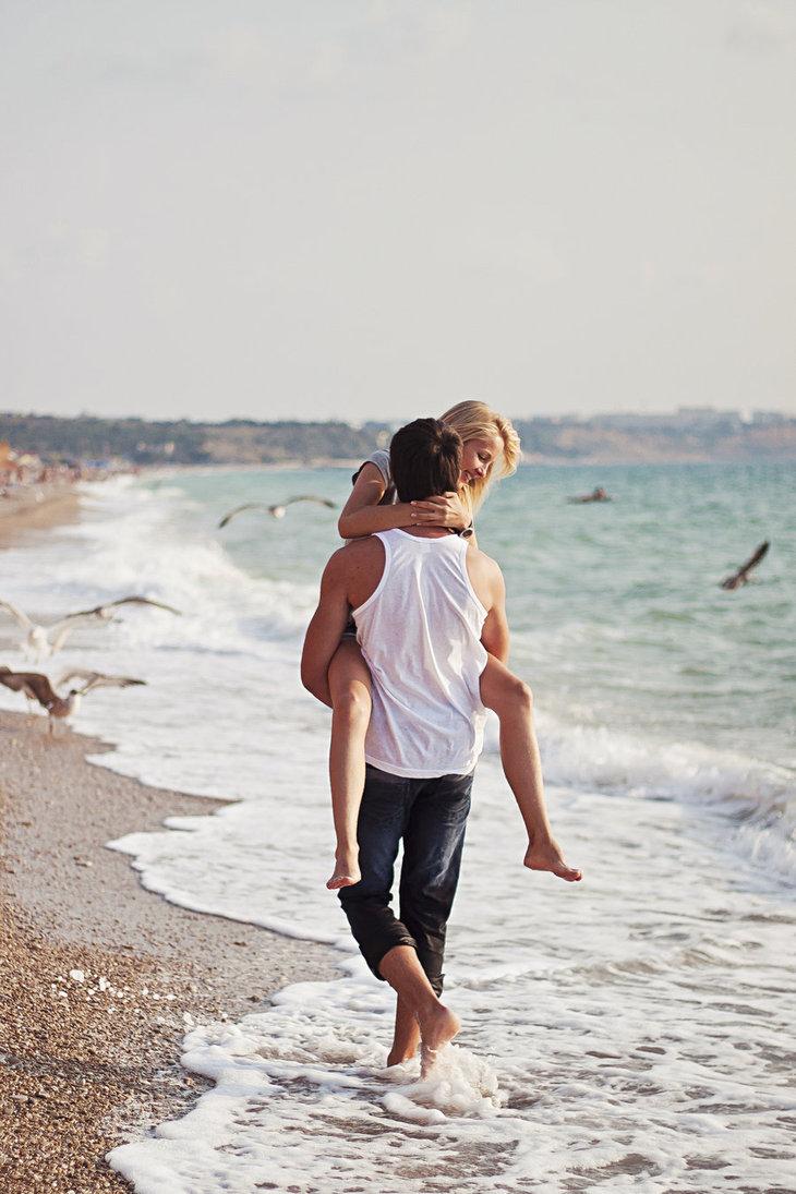 Мужчина на руках несет девушку на