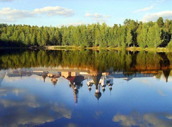 тускло сеяло за деревьями озеро