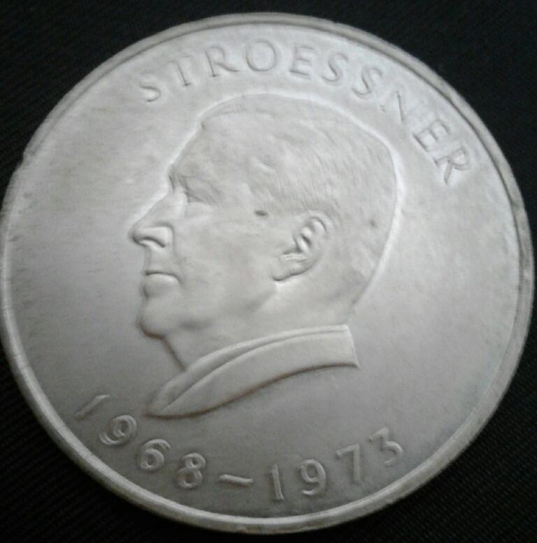 Монета Парагвая  26.6 граммов. Диаметр 38 миллиметров. Было отчеканено 250 000 таких монет. На аверсе - барельефный портрет в профиль Альфредо Стресснера (1968-1973).